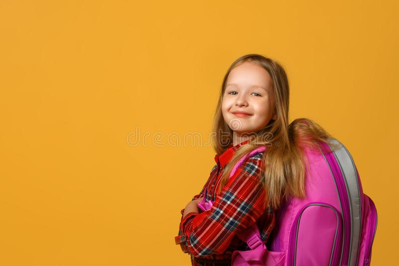 Portrait of a little girl schoolgirl on a yellow background. The child has a backpack behind his back. Back to school. royalty free stock photography