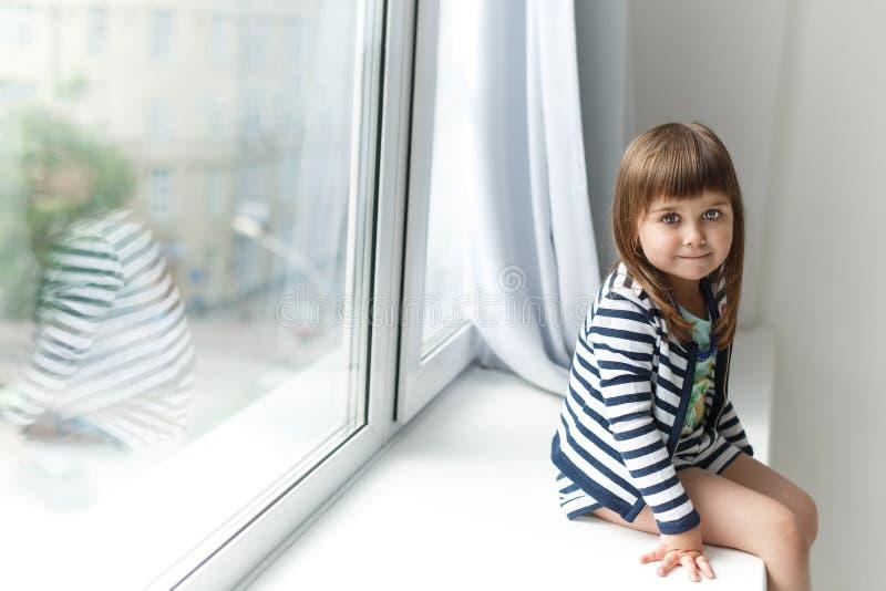 Portrait of a little girl sits on a windowsill. Portrait of a little girl sitting on a windowsill stock photos