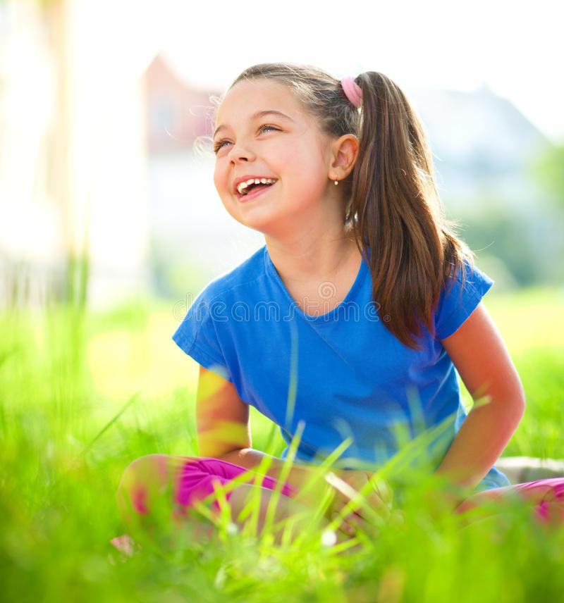 Portrait of a little girl sitting on green grass. Outdoor shoot royalty free stock photo