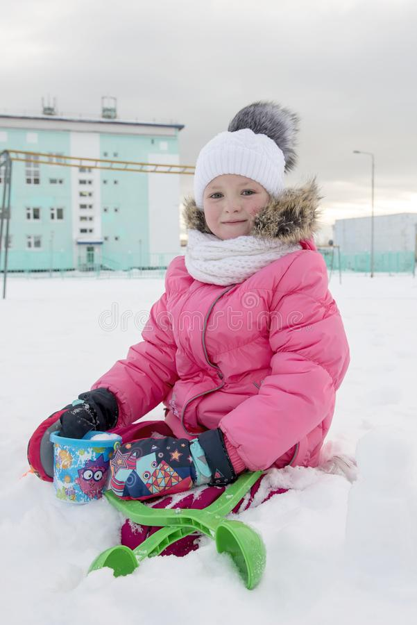 Portrait of little girl sitting on snowy ground royalty free stock photos
