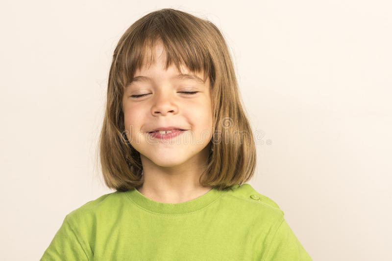Portrait of little girl. Smiling with eyes closed stock images