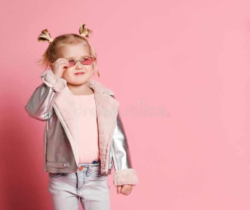 Portrait of a little girl in stylish clothing posing on pink background and playing up royalty free stock photography