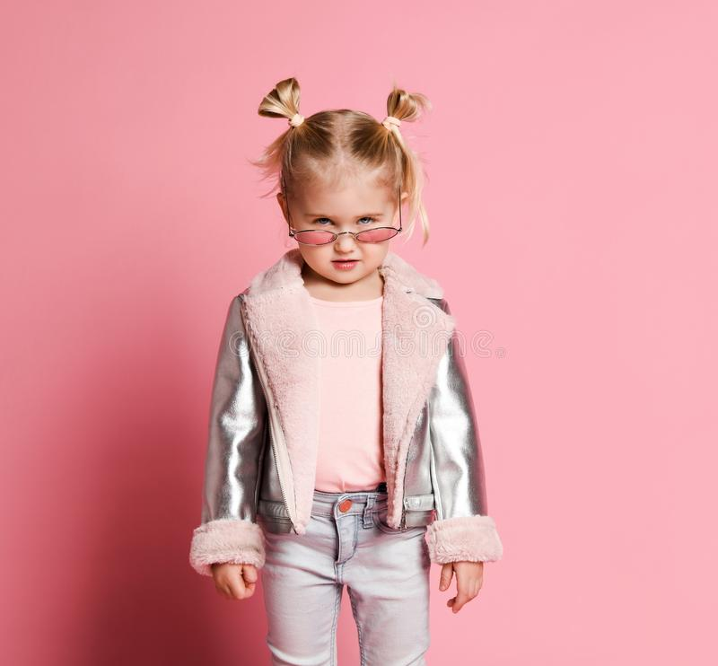 Portrait of a little girl in stylish clothing posing on pink background and playing up stock images