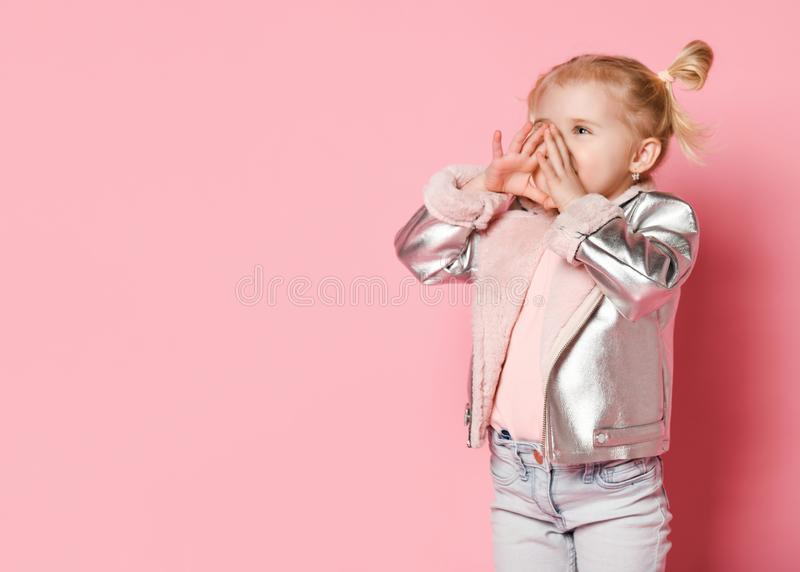 Portrait of a little girl in stylish clothing sitting on pink background and playing up stock images
