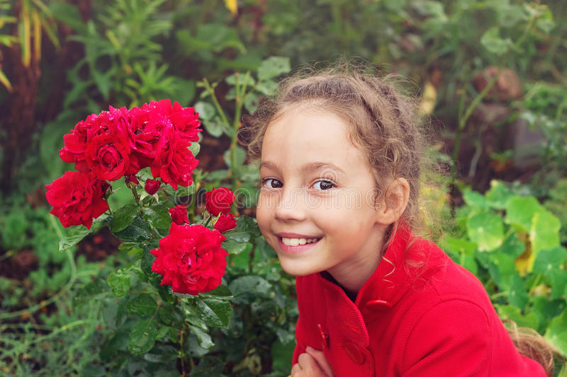 Portrait of Little Girl in the Summer time. Beautiful Girl smiling in rose Garden. Portrait of Little Girl in the Summer. Beautiful Girl smiling in rose Garden royalty free stock photography