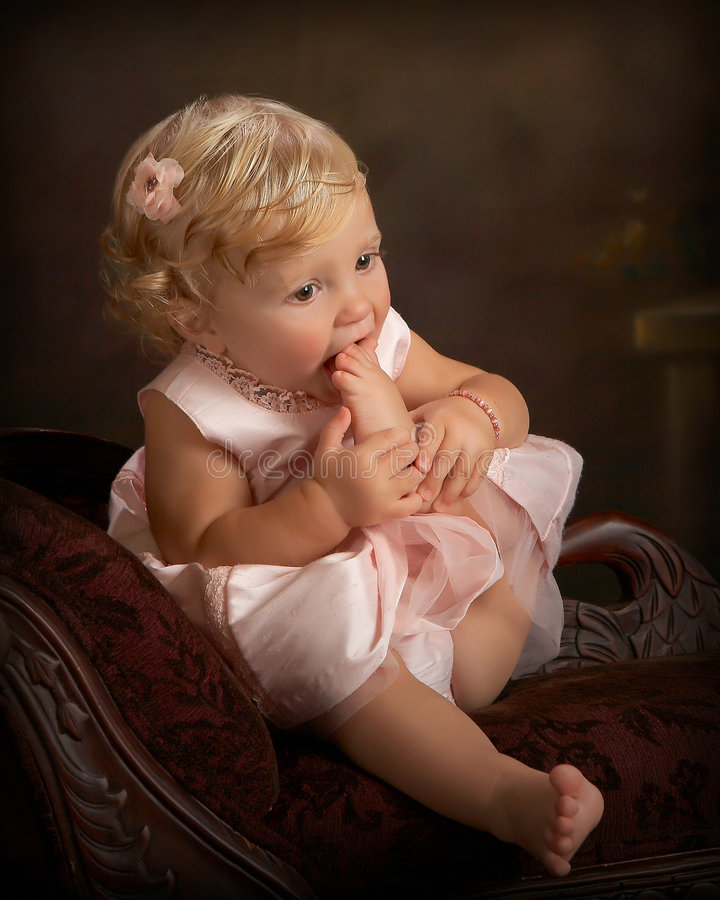 portrait of little girl with toes in mouth stock images