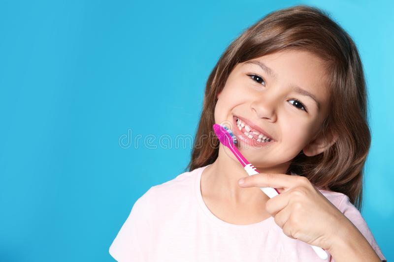 Portrait of little girl with toothbrush on color background. Space for text royalty free stock images