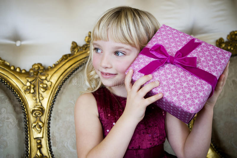 Portrait of a little girl trying to guess her birthday presents stock photo