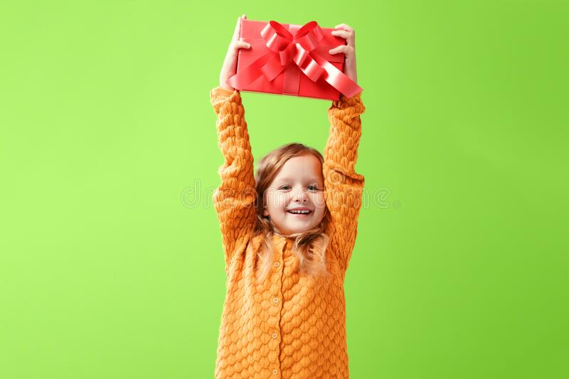 Portrait of a little girl in a warm knitted sweater on a ufo green background. A child holds a red box with a gift above his head. stock photography