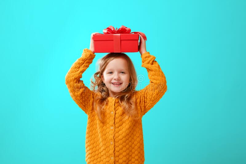 Portrait of a little girl in a warm mustard knitted sweater on a cyan background. A child holds a red box with a gift on the head. The concept of celebration stock photo