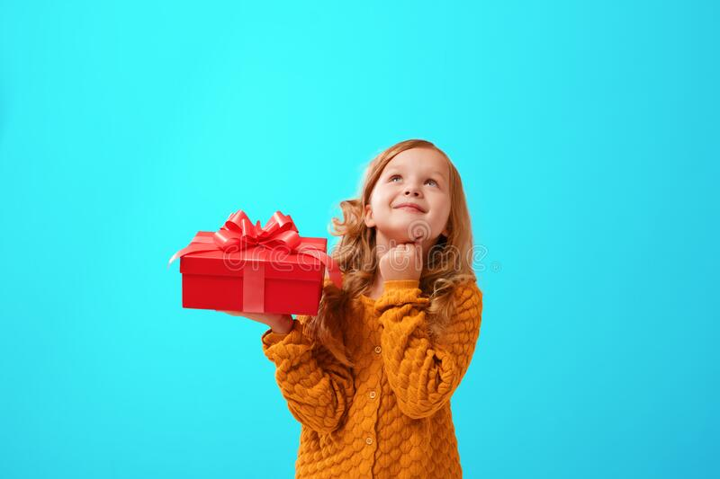 Portrait of a little girl in a warm mustard knitted sweater on a cyan background. The child looks dreamily up and holds a red gift. Portrait of a little girl in stock image