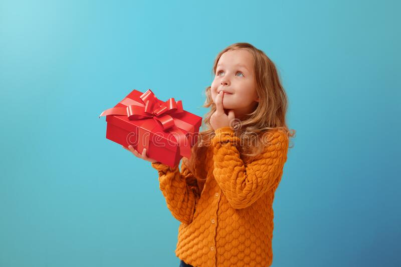 Portrait of a little girl in a warm mustard sweater on a blue isolated background. The child looks dreamily up and holds a red box stock photos