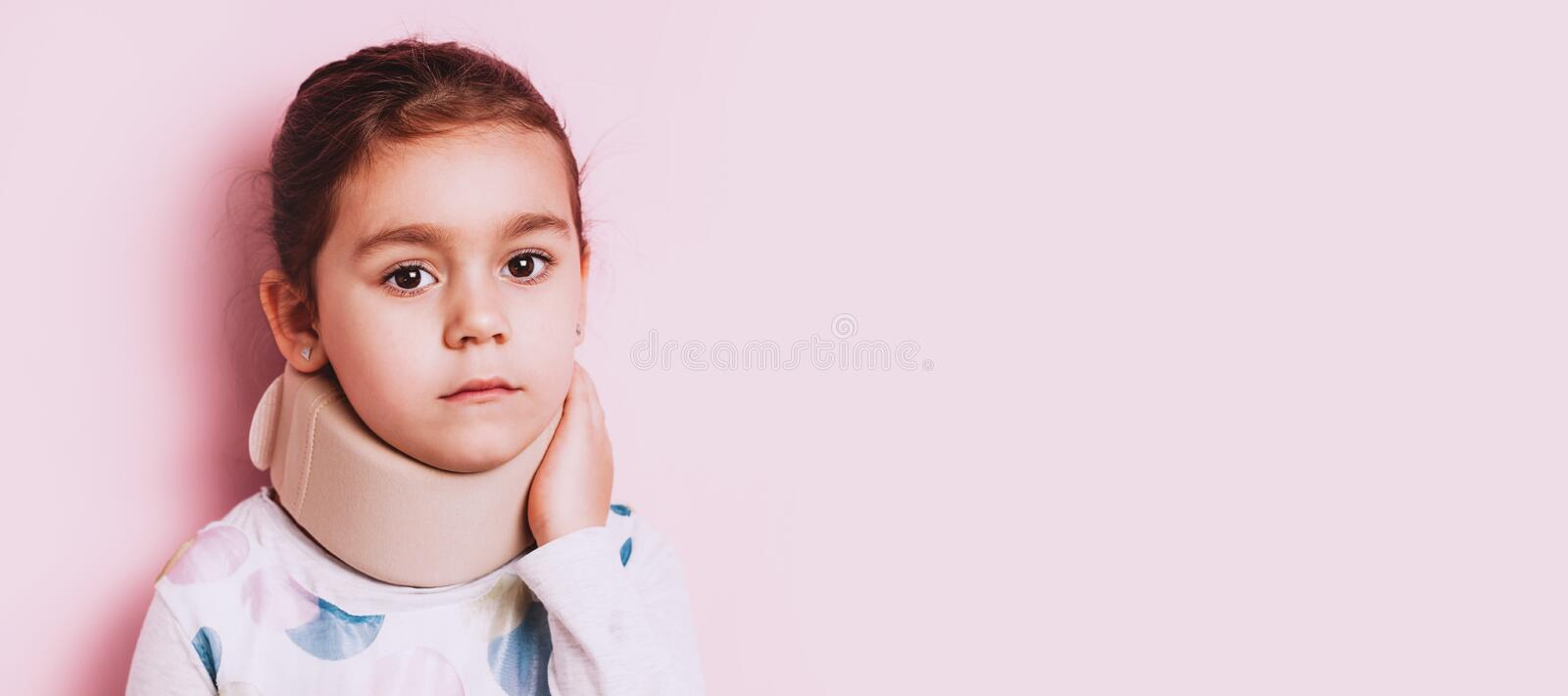Portrait of Little girl wearing neck brace on pink background. Portrait of screaming Little girl wearing neck brace on pink background. childhood injuries royalty free stock photography