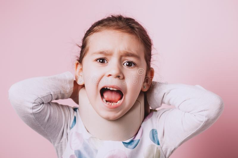 Portrait of Little girl wearing neck brace on pink background. Portrait of screaming Little girl wearing neck brace on pink background. childhood injuries stock photography
