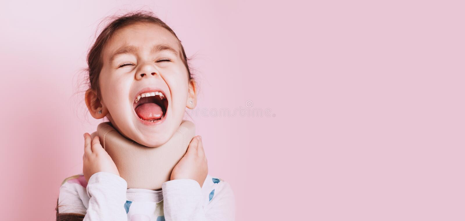 Portrait of Little girl wearing neck brace on pink background. Portrait of screaming Little girl wearing neck brace on pink background. childhood injuries stock photos