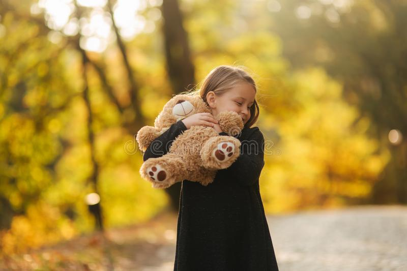 Portrait of little girl which hold teddy bear in hands. Happy child in the park. Beautiful girl model smile to camera royalty free stock images
