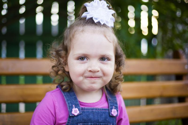 Portrait little girl with a white bow on her head smiles shyly at the camera stock photography