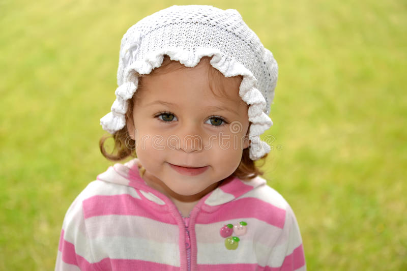 Portrait of the little girl in the white Panamanian on a green b. Ackground stock photography