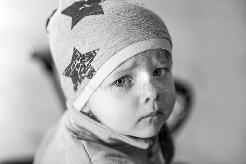 Portrait of a little girl who cries, runny nose, black and white effect. Portrait of a little girl who cries, runny nose, at home stock image