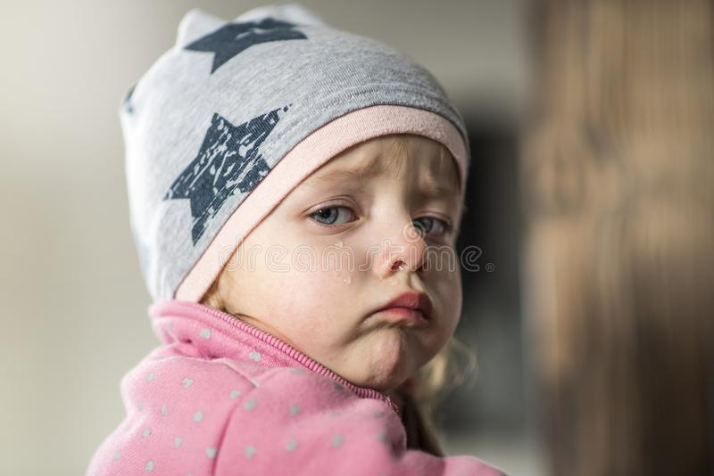 Portrait of a little girl who cries, runny nose. At home stock image
