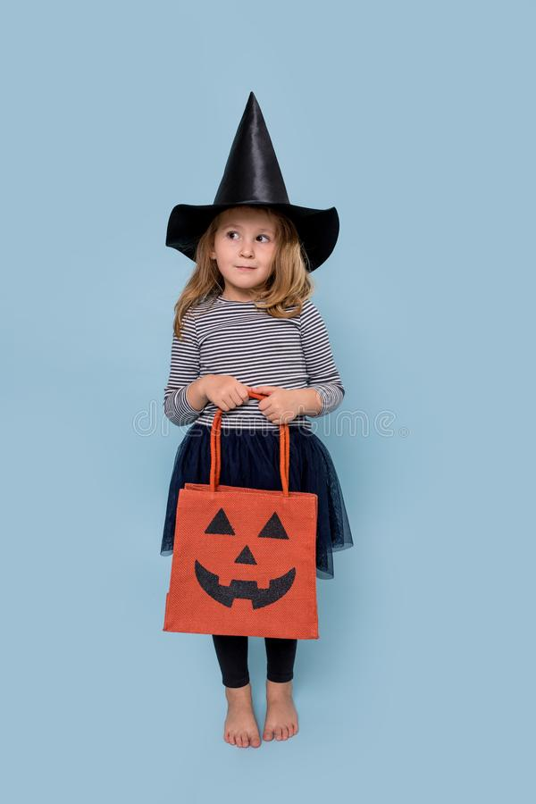 Portrait of a little girl in witch hat and black clothing holding halloween bag royalty free stock image