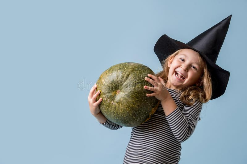 Portrait of a little girl in witch hat and black clothing with pumpkin over blue stock photography