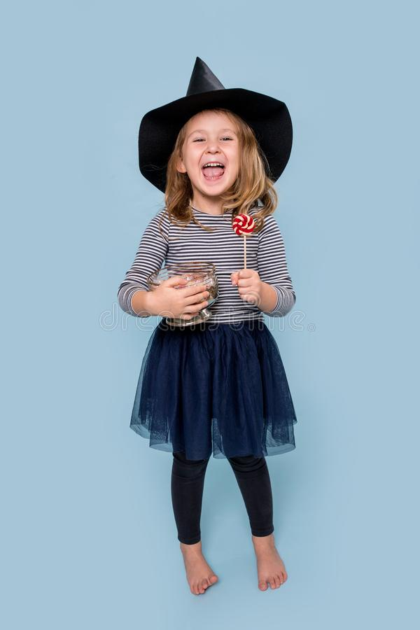 Portrait of a little girl in witch hat holding lollipop and jar full of treats stock images