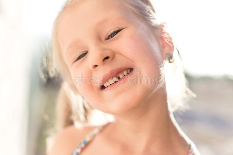 Portrait of a little girl with a wobbly baby tooth stock photos