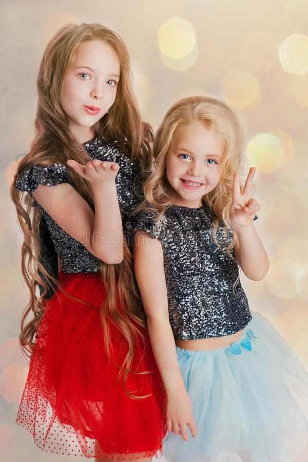 Portrait of little girls with curly hairstyle standing on the holiday party in dress with sequins. Concept Celebration stock image