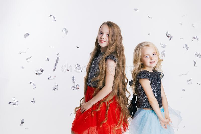 Portrait of little girls with curly hairstyle standing on the holiday party in dress with sequins. Concept Celebration. Christmas. Silver foil on the royalty free stock images
