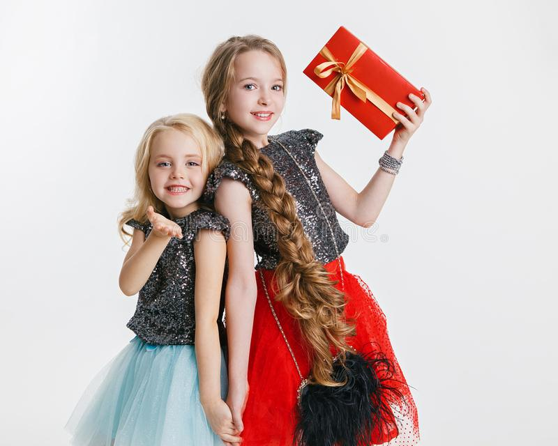 Portrait of little girls with curly hairstyle standing on the holiday party in dress with sequins, holding present. Concept Celebration. Christmas royalty free stock photos