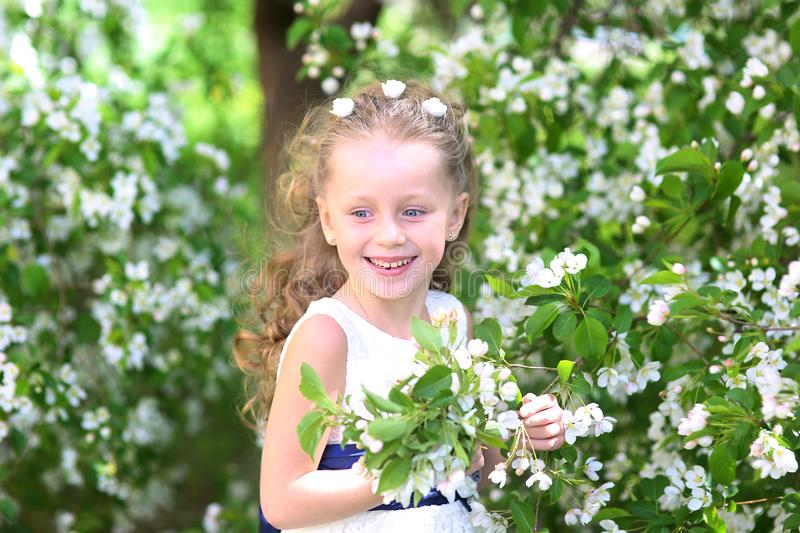Beautiful girl with long hair in a blooming garden royalty free stock images