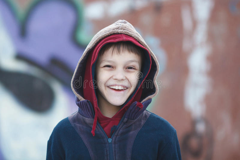 Portrait of a little happy homeless boy. Poverty, city, street, smiling stock photo