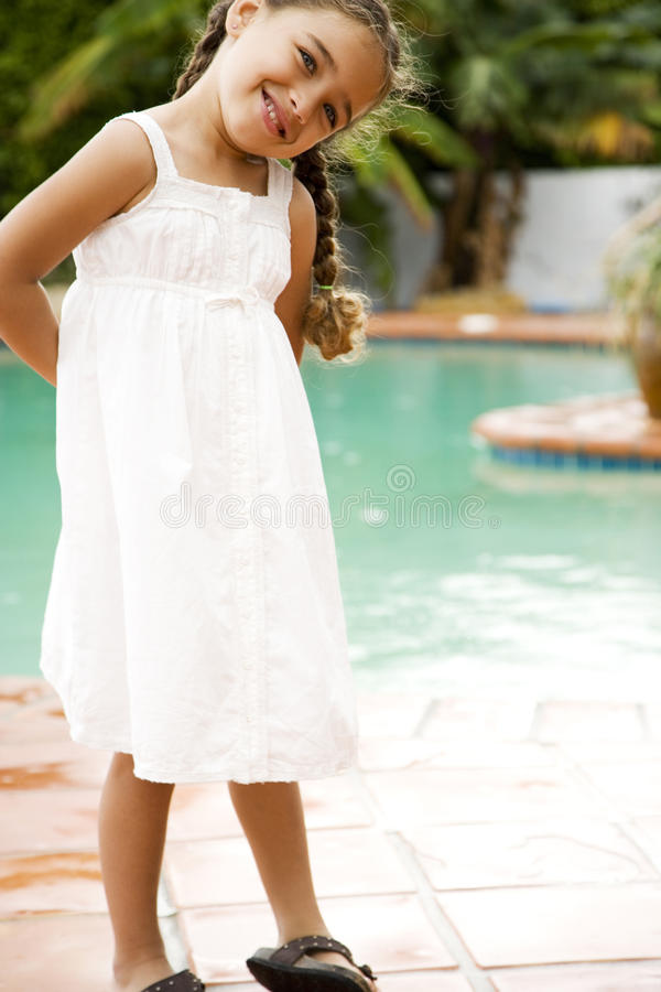 Portrait little Hispanic girl by the swimming pool royalty free stock photography