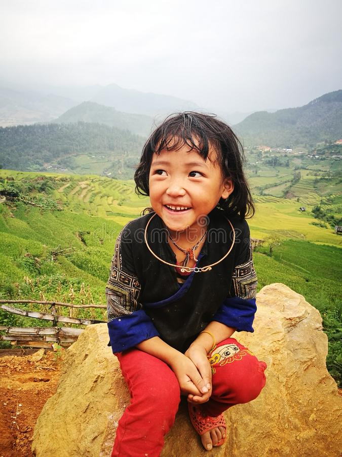Portrait of a little Hmong (Miao) minority girl sitting on a rock royalty free stock image