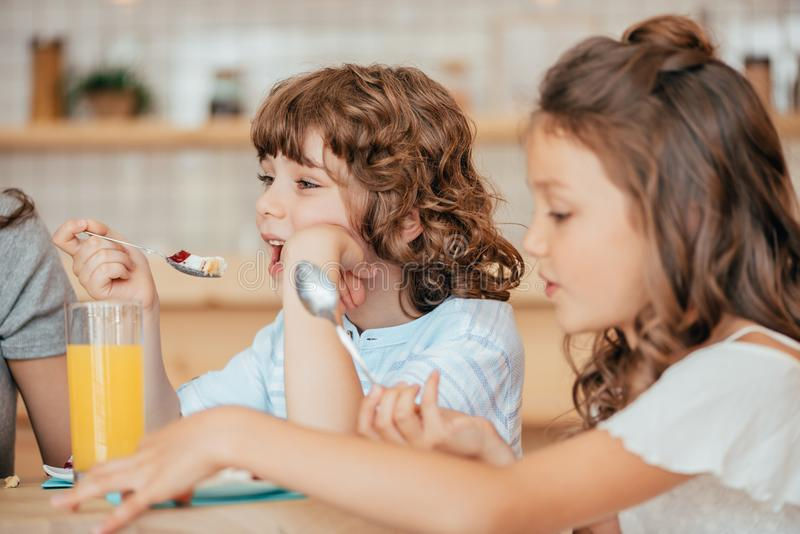 portrait of little kids eating desserts in cafe royalty free stock images