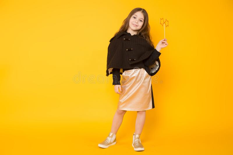 Little girl with toy star. Portrait of little long-haired girl in dress, eyeglasses and jacket isolated on orange background with copyspace holding stars on royalty free stock images