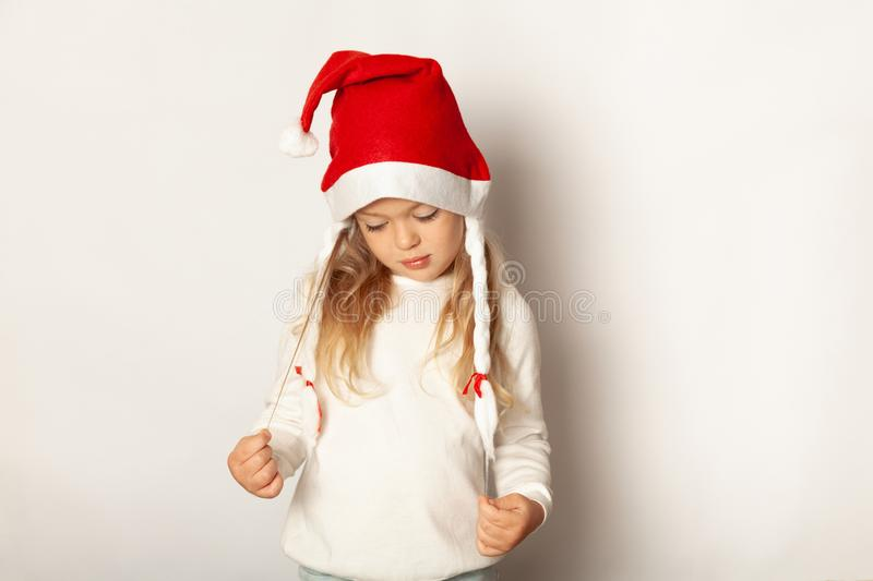 Portrait of little pretty girl upset in Santa hat. Dissatisfied with gift for New Year, Christmas stock photography