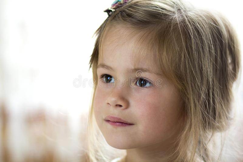 Portrait of little pretty young child girl with gray eyes and clip in scattered fine blond hair looking dreamily in distance on bl. Urred sunny background stock photo