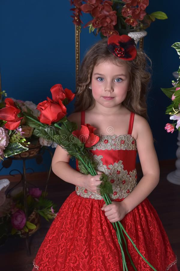 Portrait of a little princess girl in a red dress with flowers i stock photo