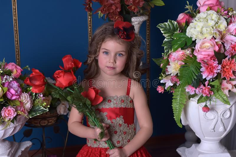 Portrait of a little princess girl in a red dress with flowers i royalty free stock photography