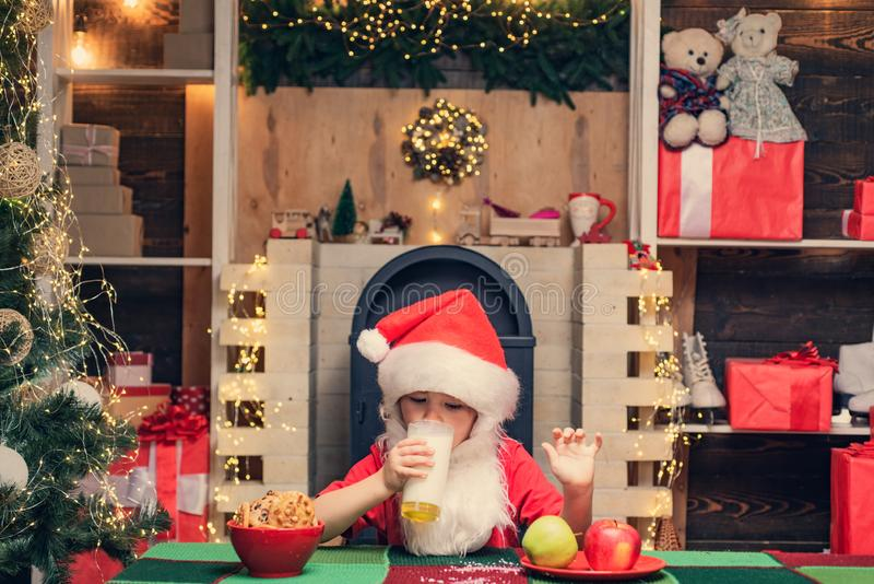 Portrait of little Santa child holding chocolate cookie and glass of milk. Christmas food and drink. Kid Santa Claus stock photo