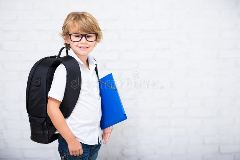 Portrait of little school boy in glasses with backpack and space stock photo