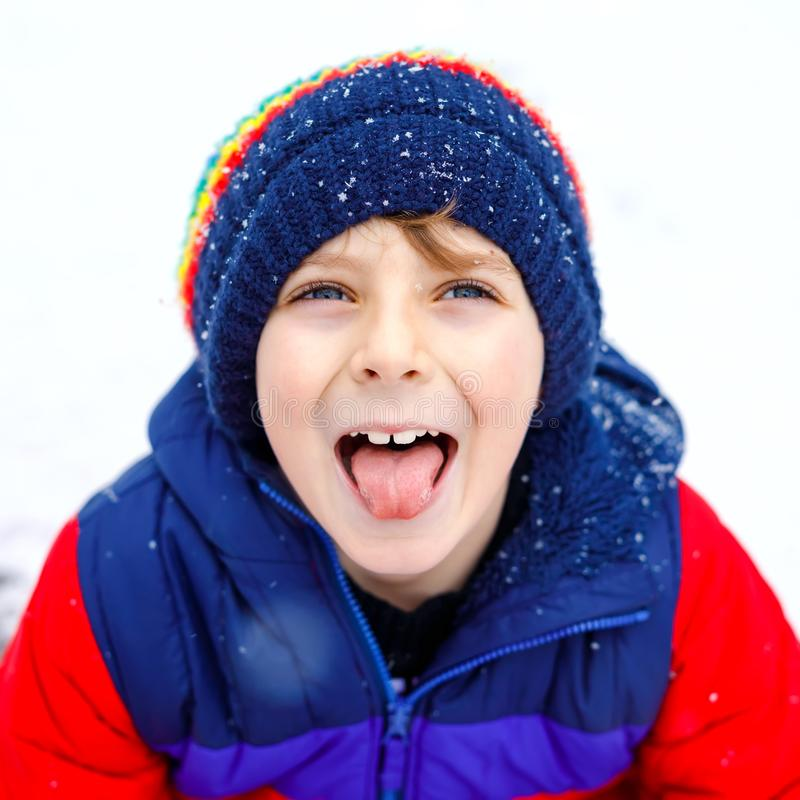 Portrait of little school kid boy in colorful clothes playing outdoors during snowfall. Active leisure with children in stock images