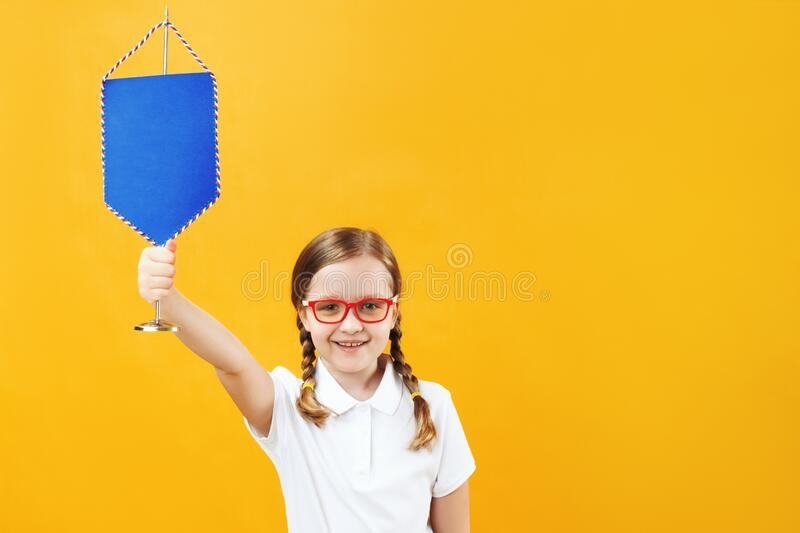 Portrait of a little schoolgirl girl in glasses on a yellow background. The child holds a pennant in his hands. The concept of education, success, achievement royalty free stock photography