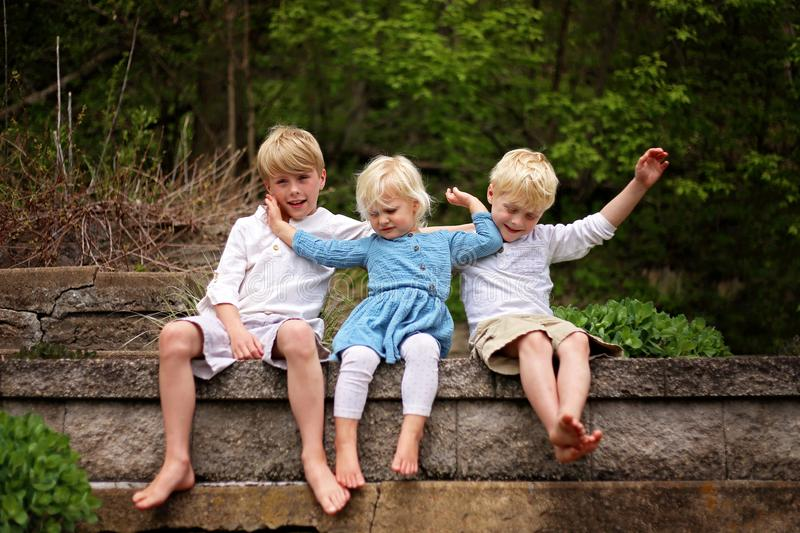 Portrait of Little Sister Child Pushing her Brothers Away. Three cute children are posing for a portrait outside, but the little sister is pushing her big royalty free stock photo