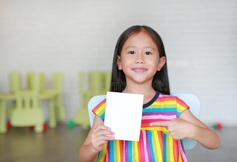 Portrait little smiling Asian child girl holding blank white paper card in her hand with pointing. Kid showing empty paper note. Copy space in children room royalty free stock image