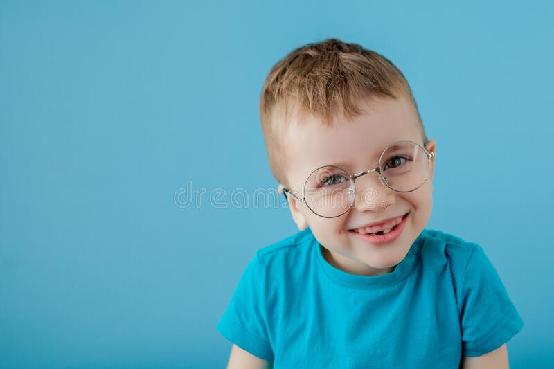 Portrait of a little smiling boy in a funny glasses. School. Preschool. Fashion. Studio portrait on a blue background, copy space royalty free stock photography