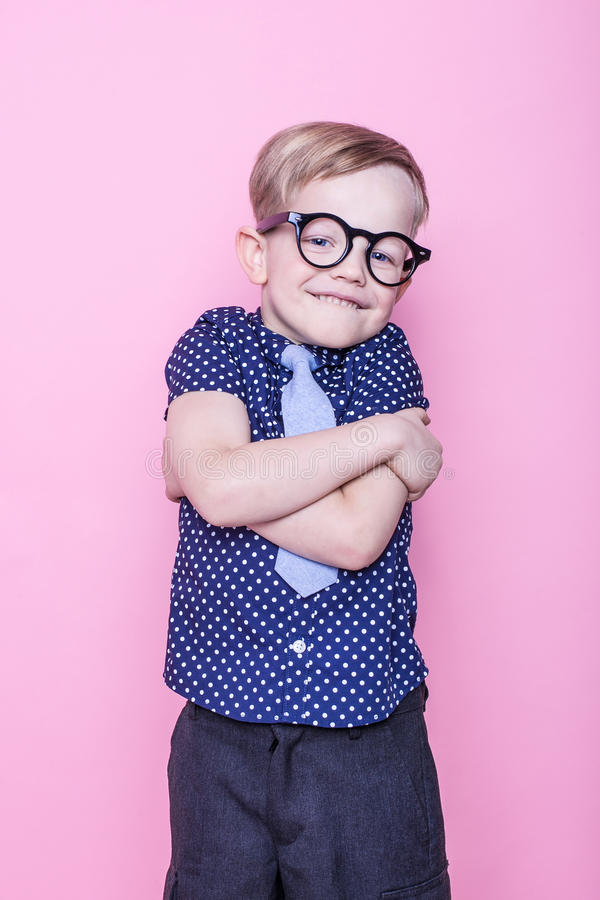 Portrait of a little smiling boy in a funny glasses and tie. School. Preschool. Fashion. Studio portrait over pink background. Stylish boy in shirt and glasses royalty free stock photos