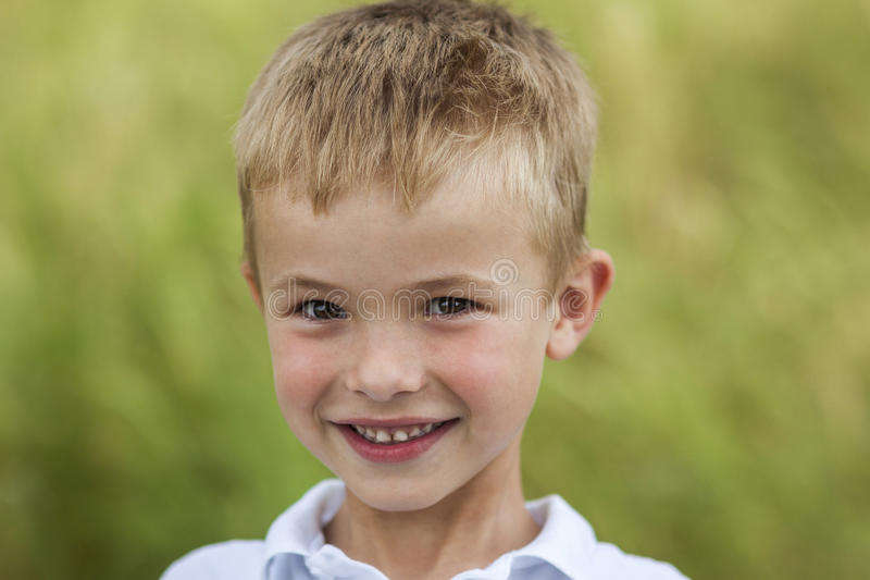 Portrait of a little smiling boy with golden blonde straw hair i. N sunny summer day on green blurred stock image